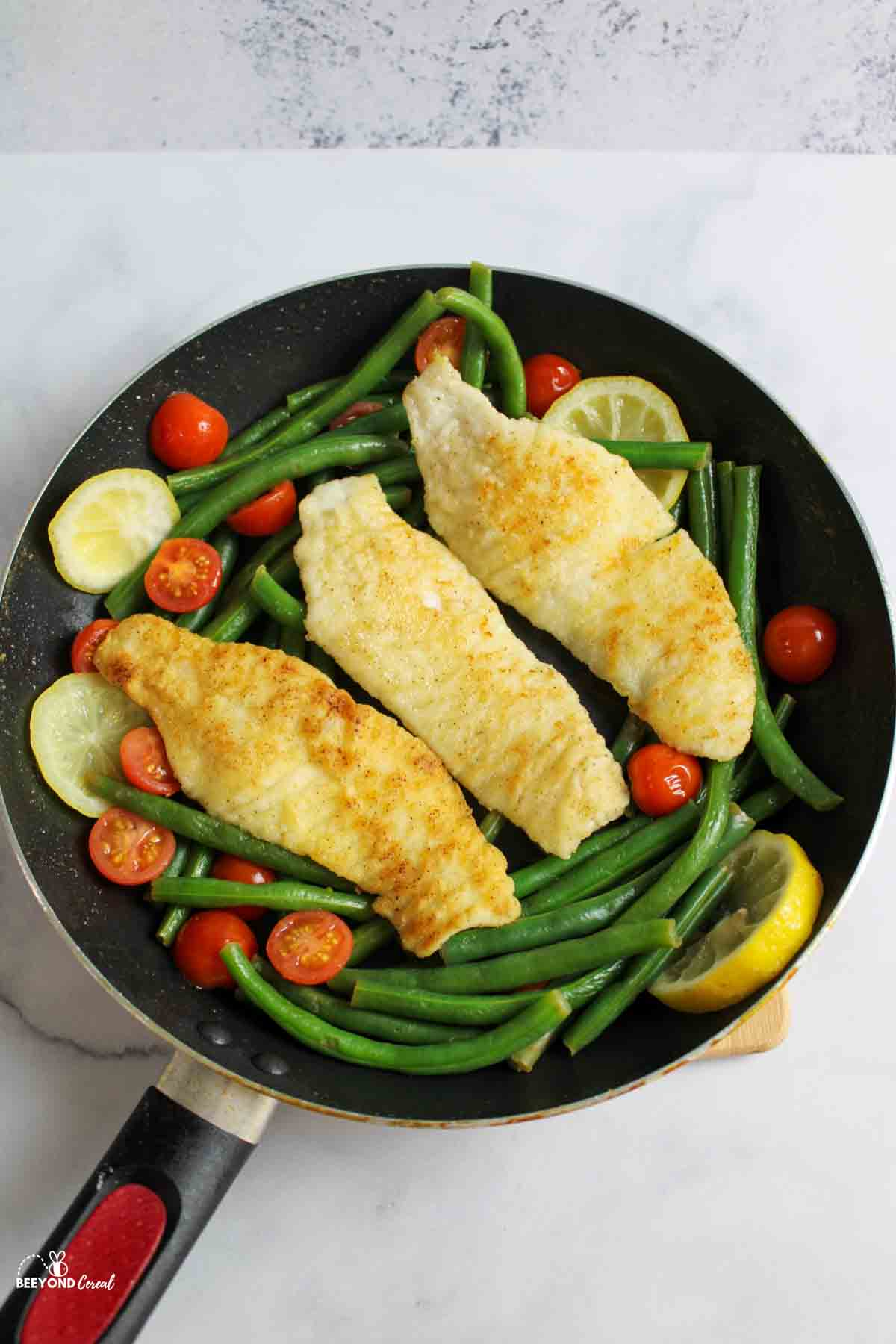three tilapia fillets, green beans, cherry tomatoes and lemon slices in a skillet