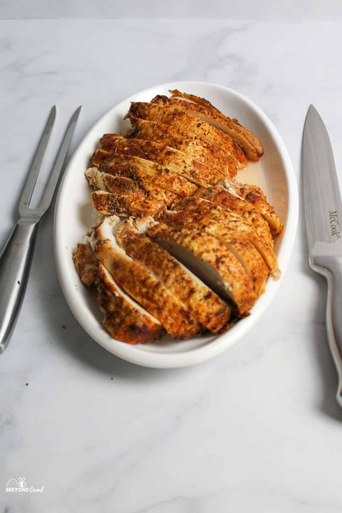 sliced turkey breasts on platter with carving tools to the sides