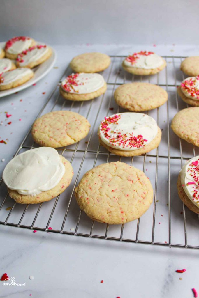 cherry chip cookies on a wire rack in both plain and frosted and sprinkle options