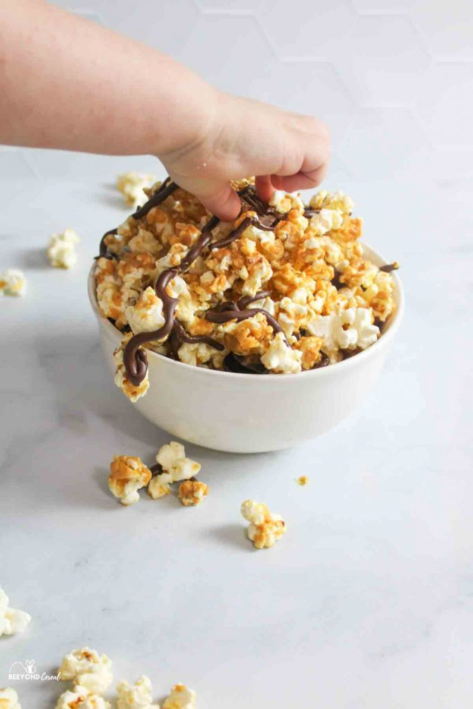 a hand reaching in for a piece of chocolate peanut butter popcorn