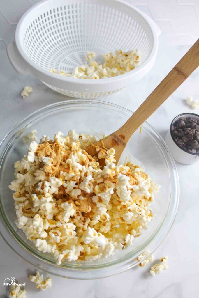 mixing peanut butter mixture with popcorn