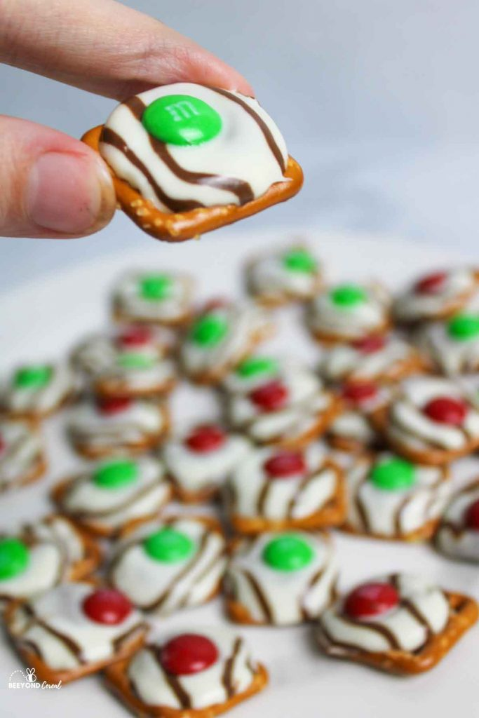fingers holding up a green M&M topped christmas pretzel