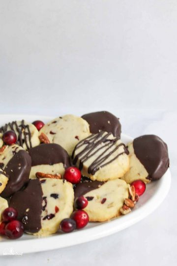 chocolate dipped shortbread cookies on platter with whole fresh cranberries