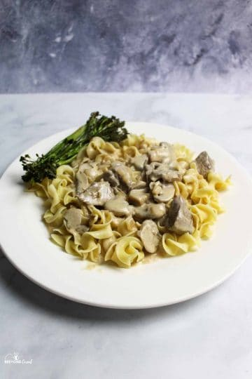 a white plate with creamy stroganoff on egg noodles and broccolini in back