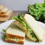 two halves of egg salad sandwich on a white plate stacked on top of another