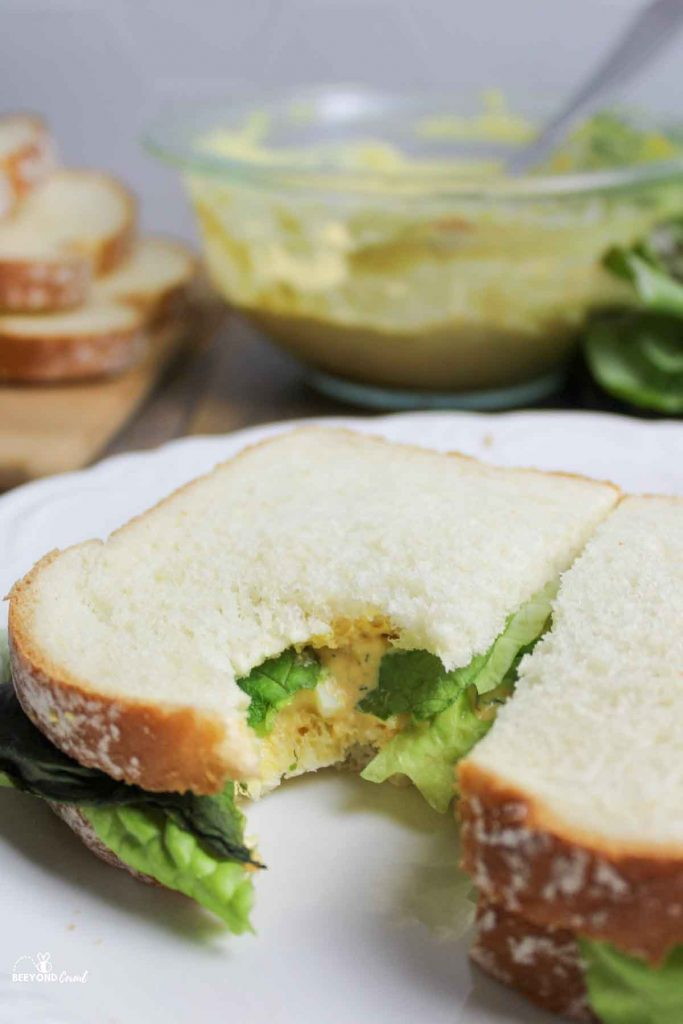 an egg salad sandwich with a bite missing