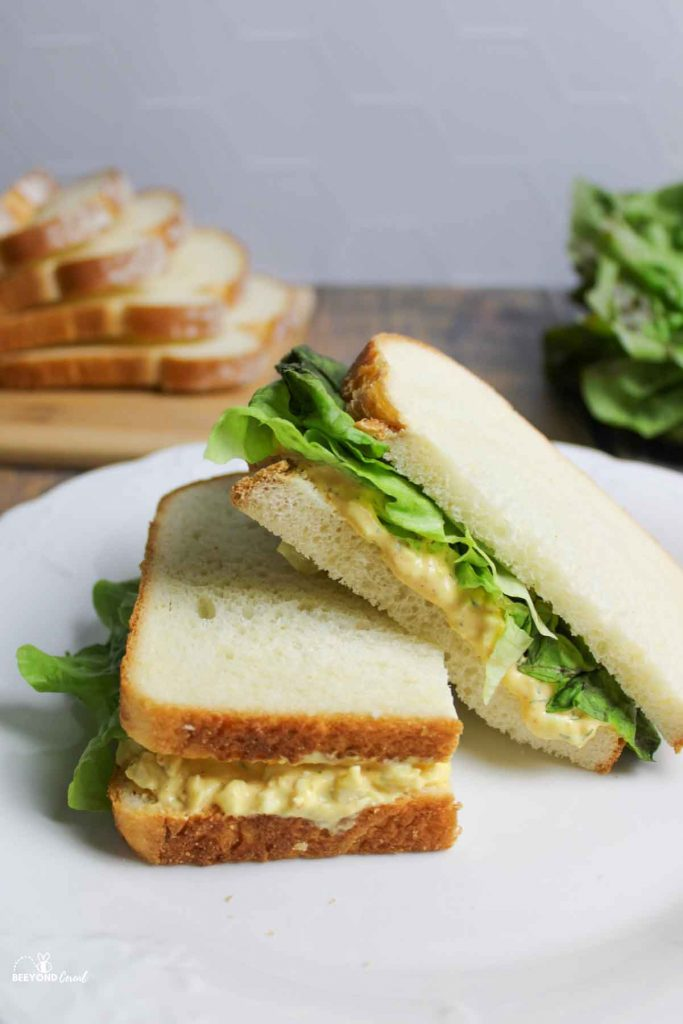 a half of an egg salad sandwich resting off of the other