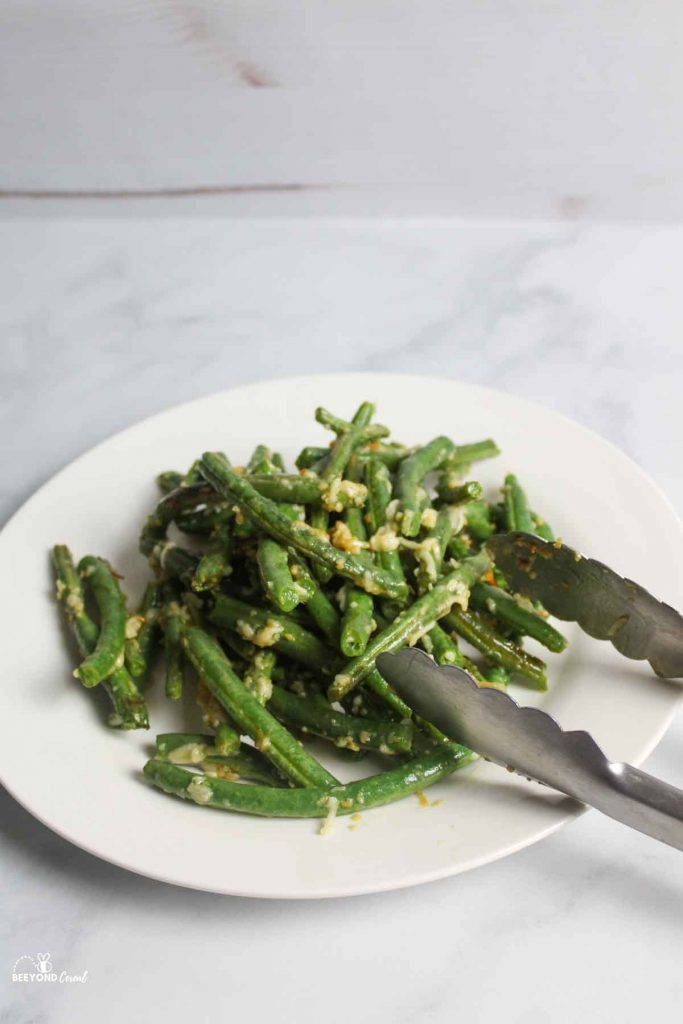 cooked green beans on white plate