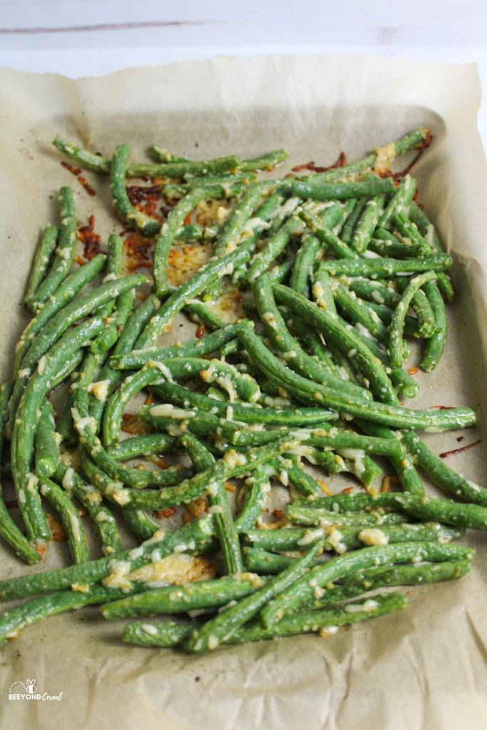 cooked green beans on parchment lined baking sheet