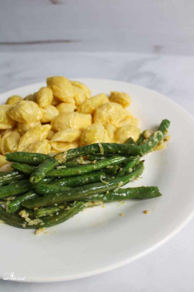 close up view of cooked green beans on a plate with mac and cheese