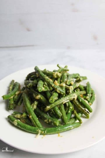 a close up of a pile of cooked green beans on a white plate