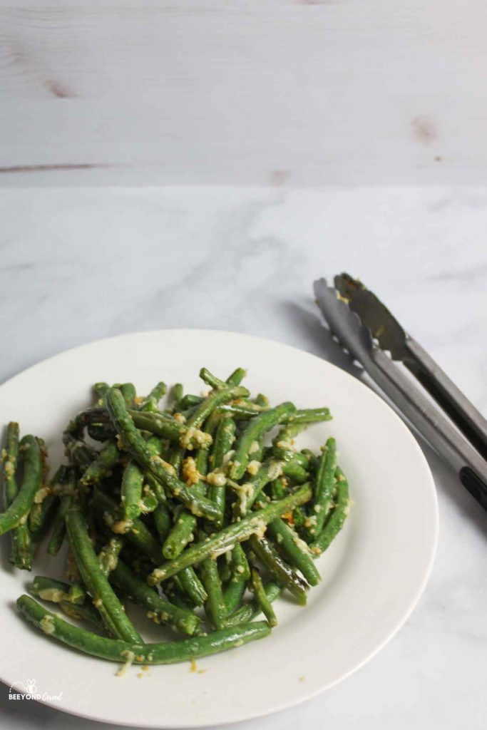 green beans on white plate with metal tongs to the side