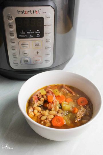 a bowl of ham and bean soup in front of the instant pot