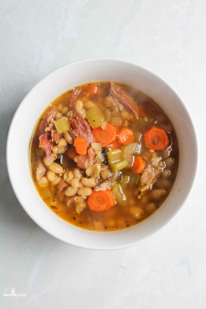 aerial view of ham and bean soup in white bowl