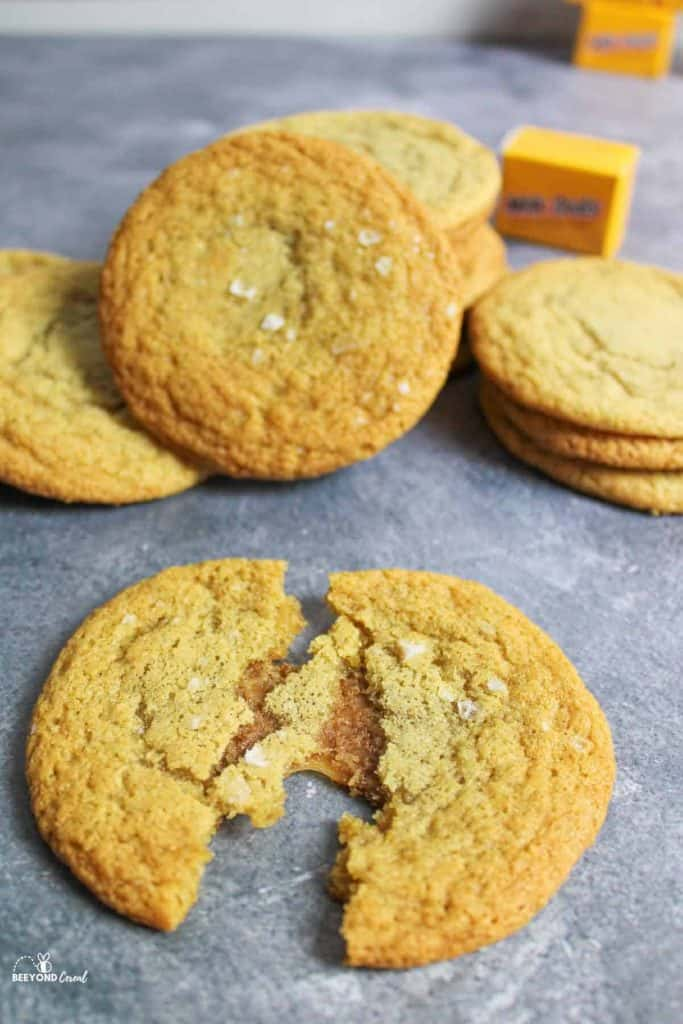 milk dud stufed cookies piled together with one in front broken open to reveal gooey chewy caramel inside