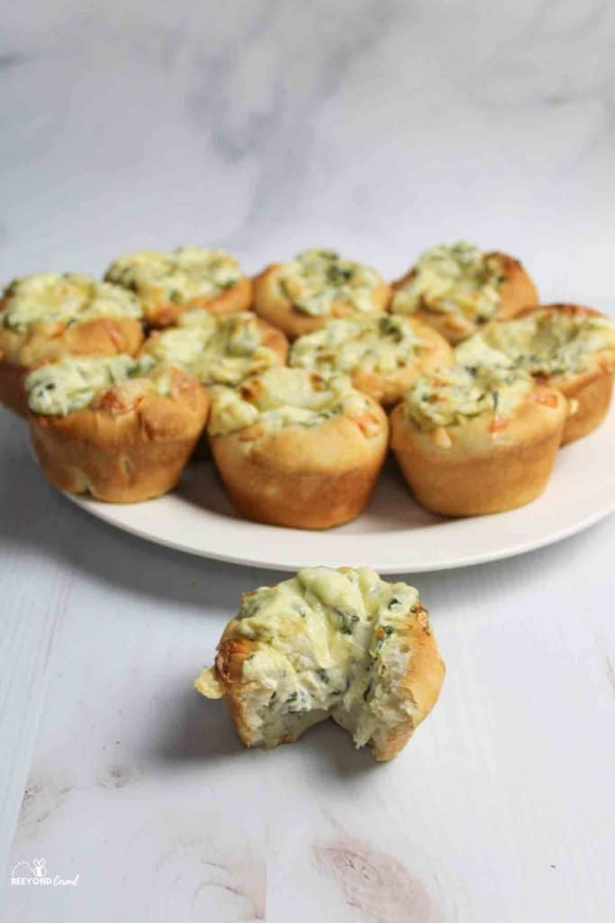 a plate of spinach dip muffins with one in front missing a bite