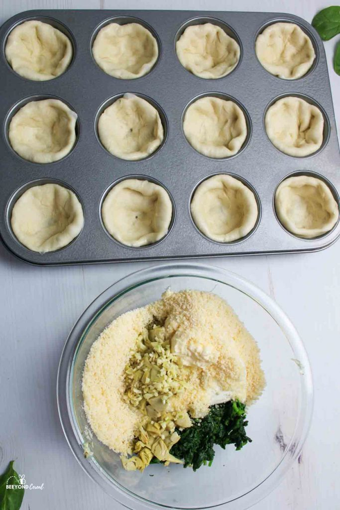 bread dough bowls in a muffin tin next to a bowl of ingredients for the dip