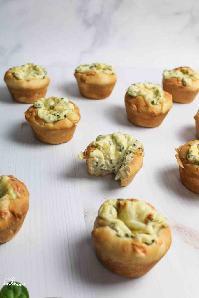 spinach dip cups scattered with one missing a bite in the center