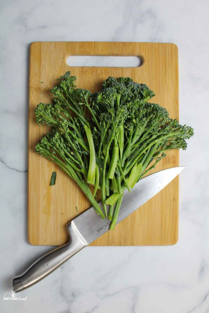 a cutting board with the ends sliced off of broccolini and a large knife resting beside the bundle