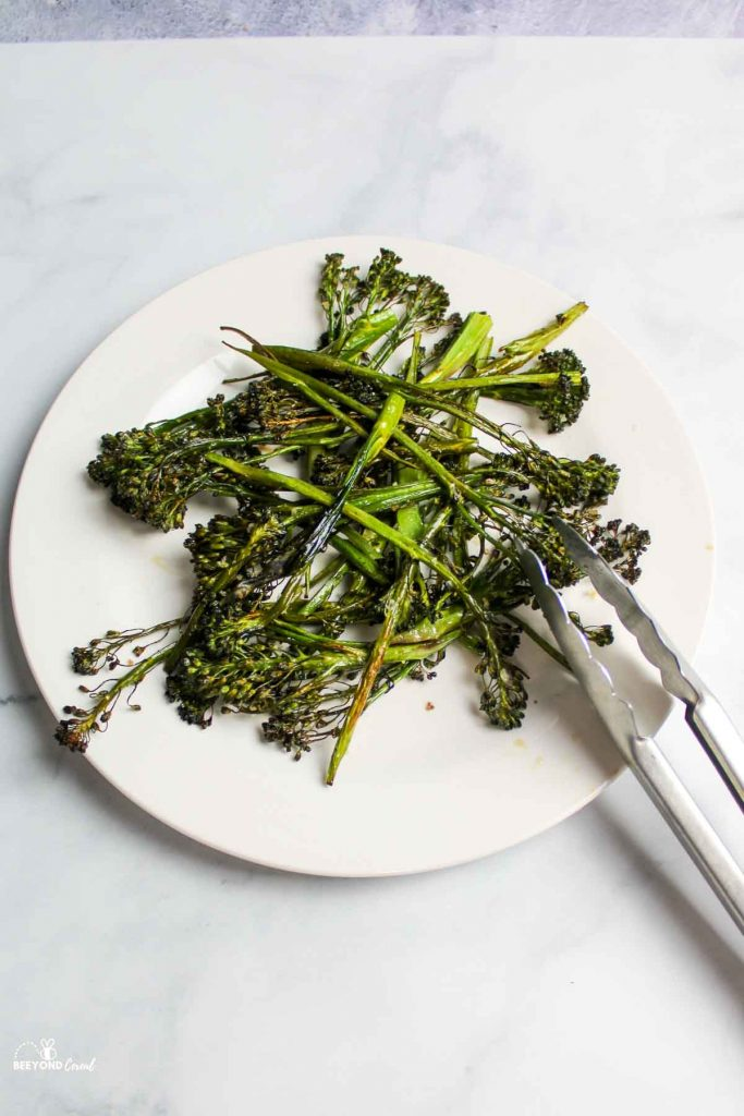 a plate or roasted broccolini with metal tongs resting off of the side