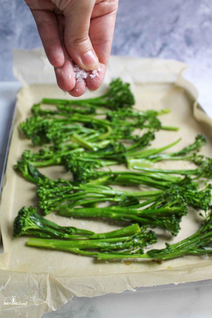 a hand sprinkling salt onto the broccolini