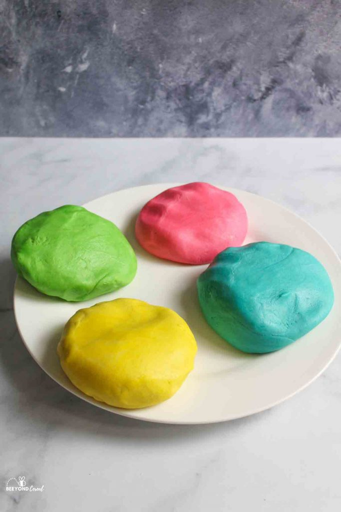 4 divided and colored balls of cookie dough