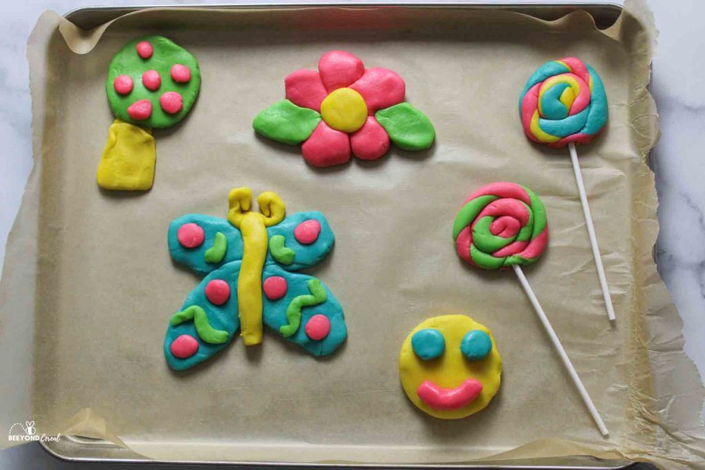 raw playdoh cookies on parchment lined baking sheet