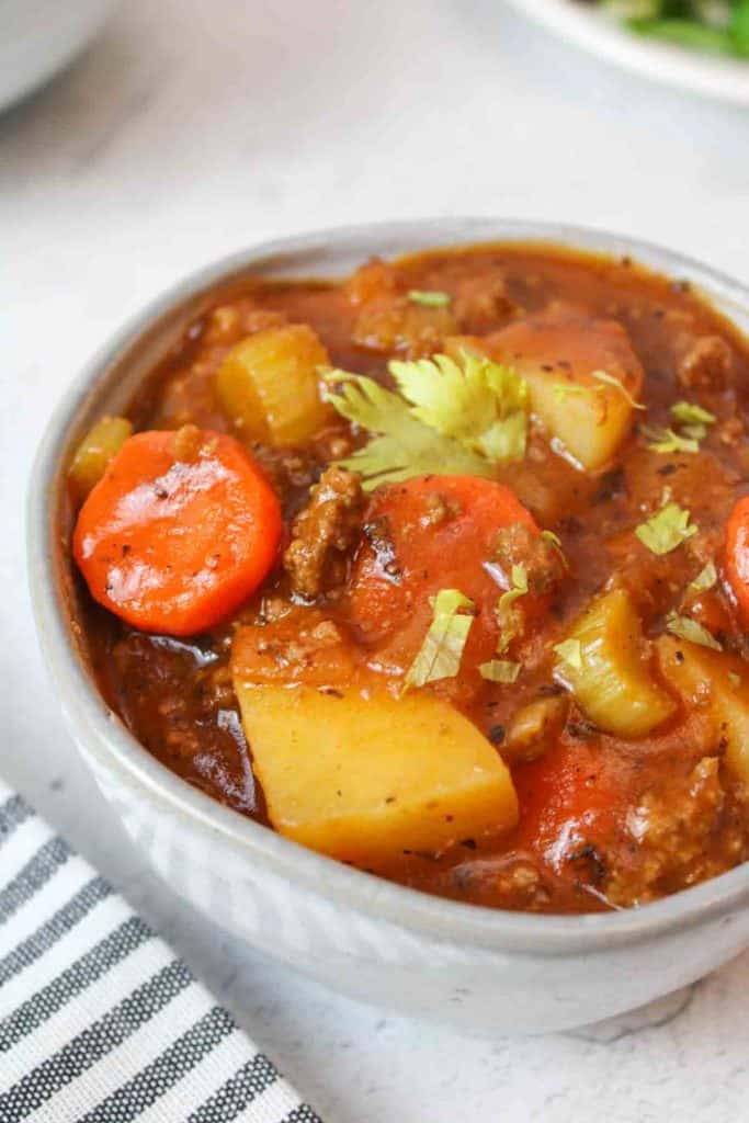 a bowl of stew with spoons and empty bowls to the sides