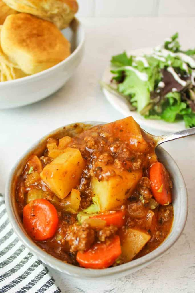 two bowls of stew next to a red pot