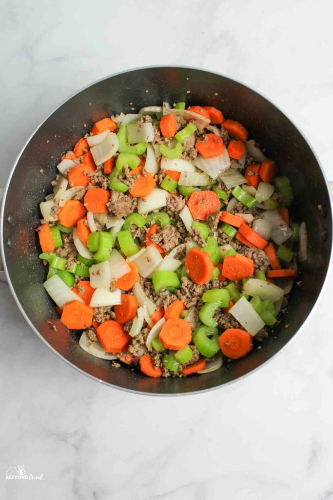 cooked ground beef with celery, onion, and carrots in a pot