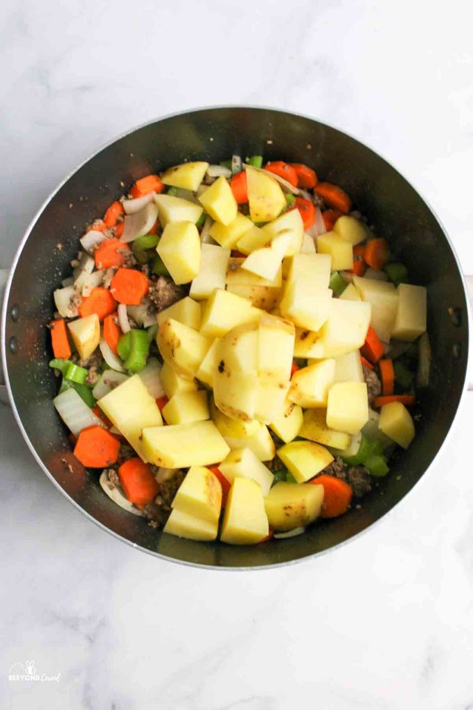 adding potatoes to the pot of meat and veggies