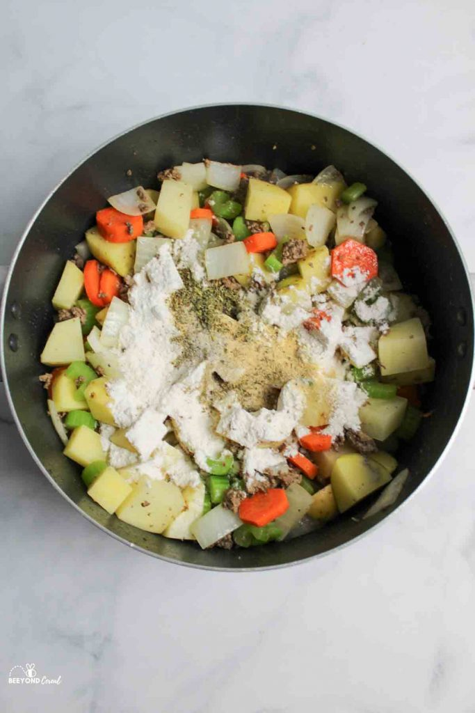 flour and seasonings being added to veggie and meat mix in pot