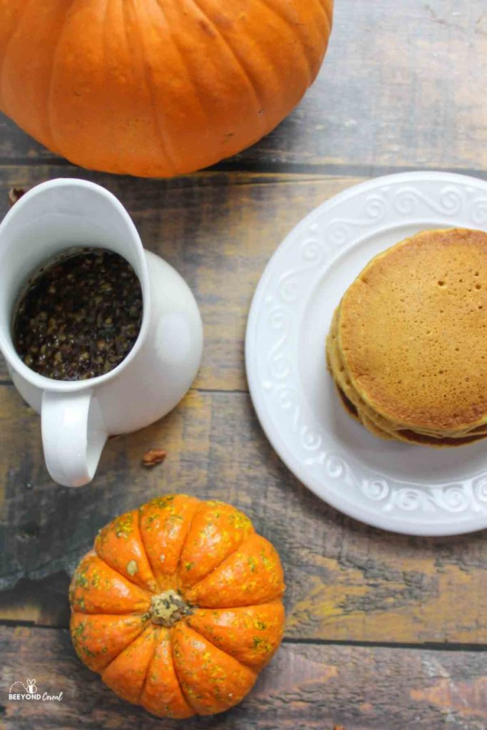 a pitcher of butter pecan syrup and a stack of pumpkin pancakes