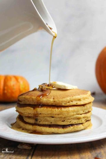 pouring homemade syrup on a stack of pancakes