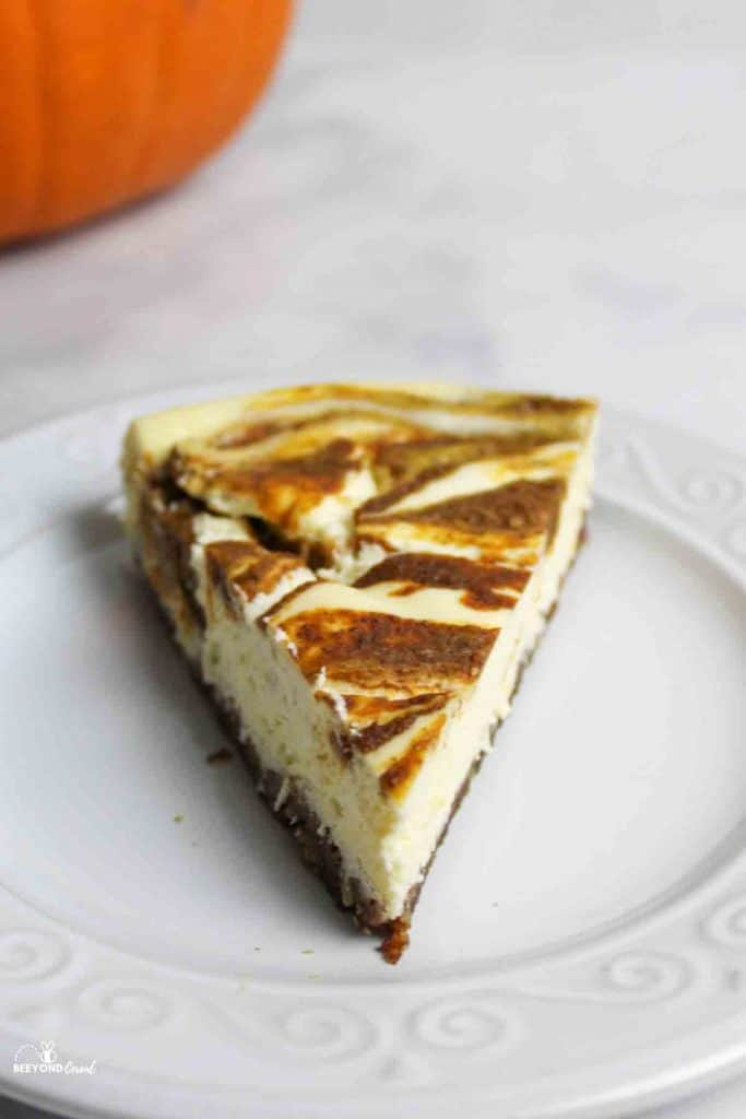 a pumpkin cheesecake slice on a white plate with more cheesecake and a pumpkin in back