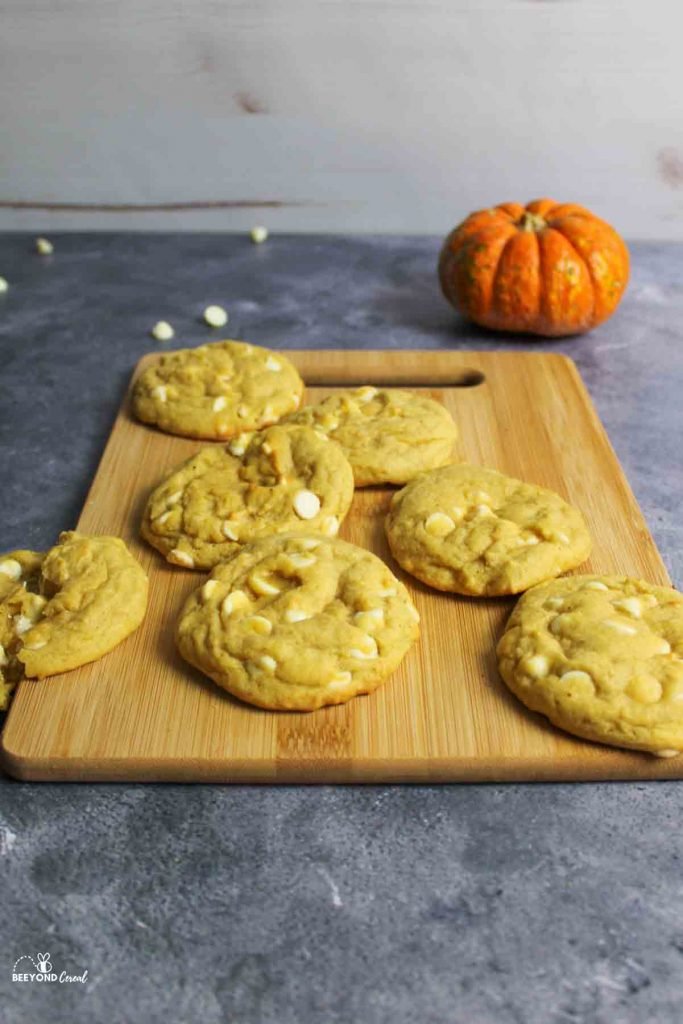 cookies scattered on a cutting board in front of a small pumpkin