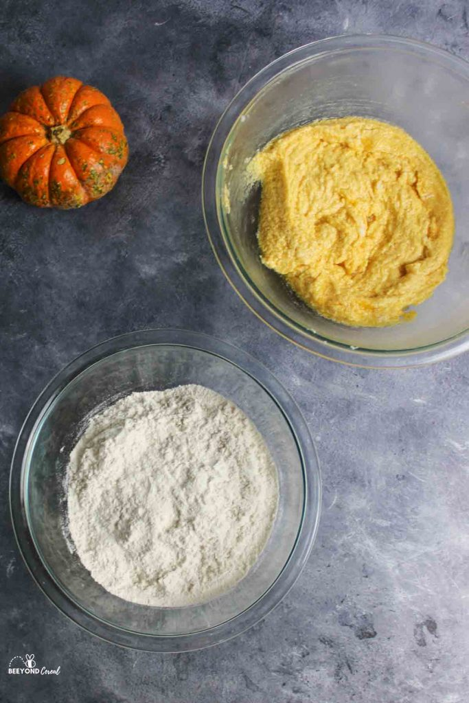 wet ingredients in one bowl and dry in another with a pumpkin to the side