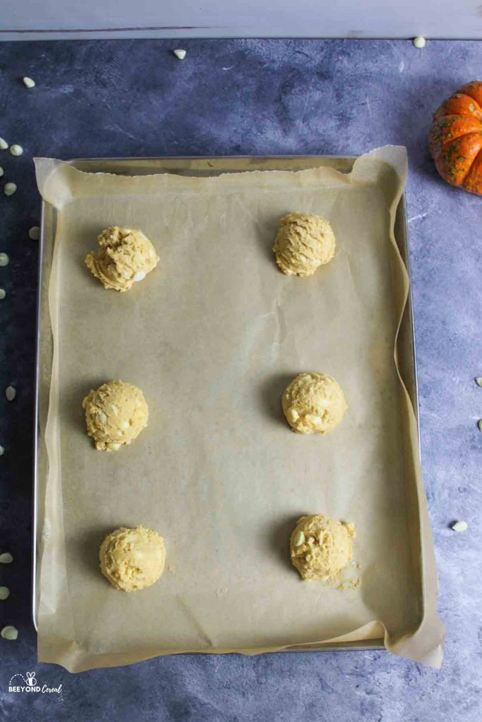 scooped cookie dough on parchment lined baking sheet