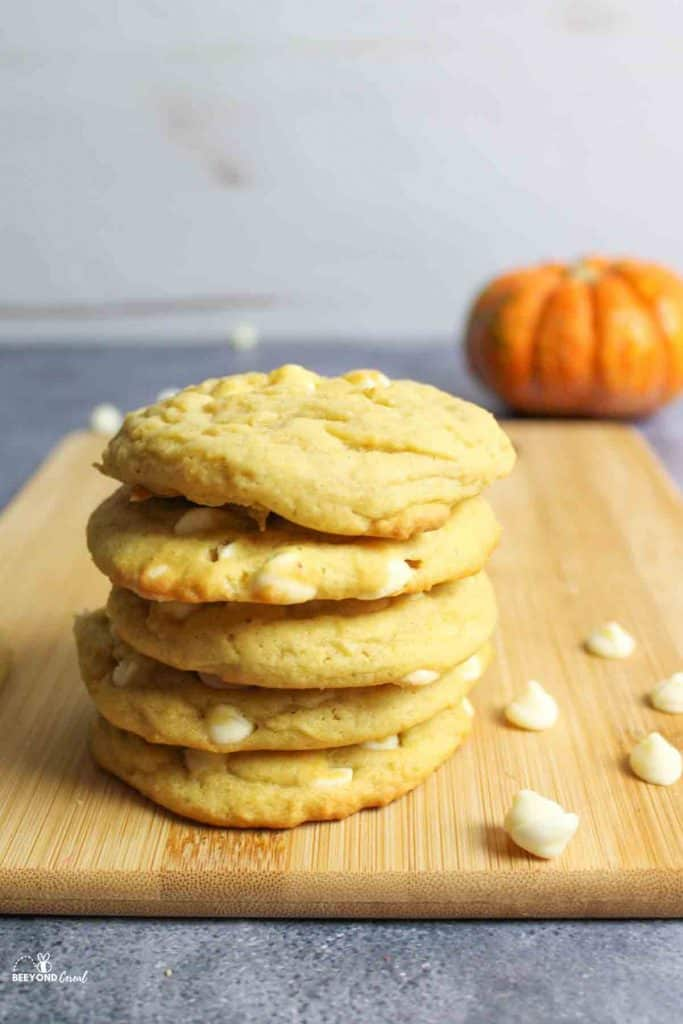 a stack of pumpkin white choc chip cookies with scattered choc chips around and a pumpkin in back