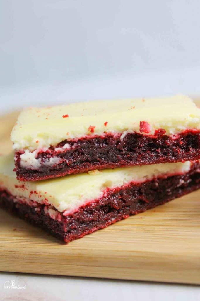 red velvet cheesecake brownie stacked two high on wooden cutting board
