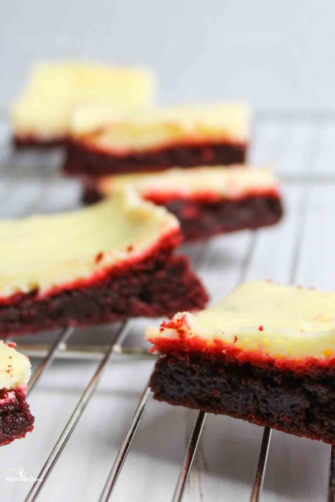 red velvet cheesecake brownie squares scattered on wire rack