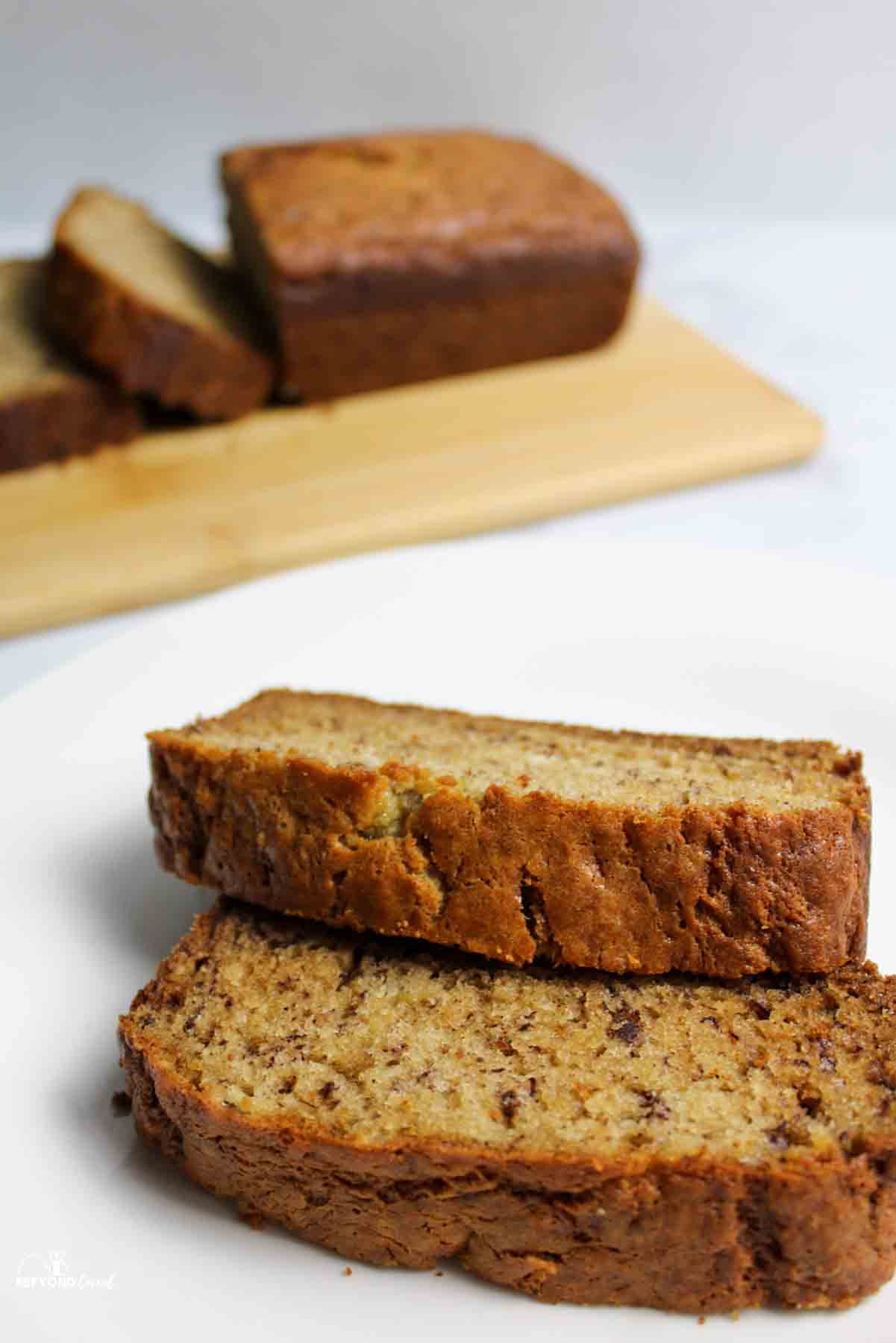 two slices of banana bread with more banana bread sliced in back