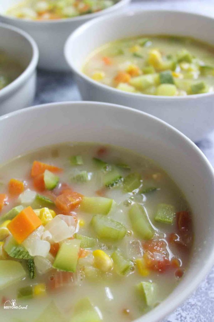 a close view of bowls filled with zucchini corn chowder