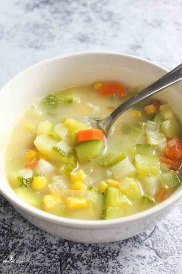a bowl filled with zucchini corn chowder