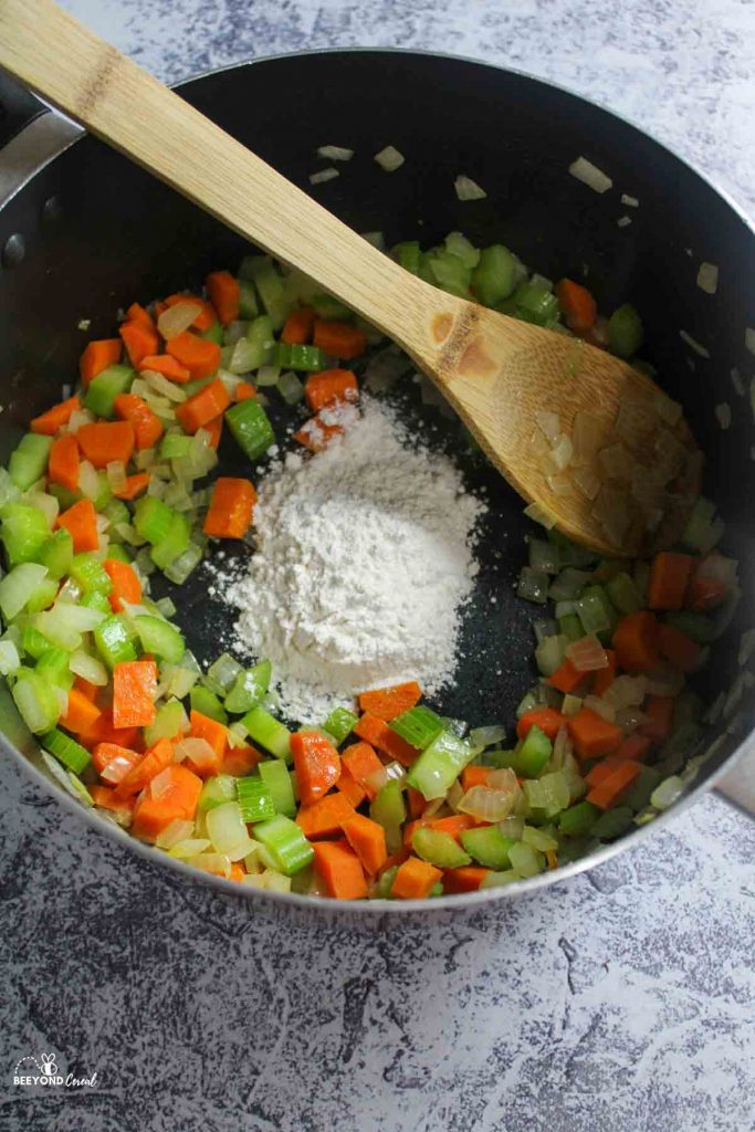flour added to a pot of celery carrots and onions