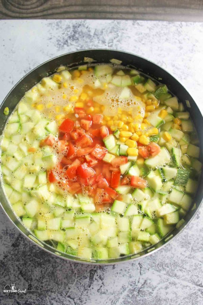an aerial view of a large pot filled with veggies and broth