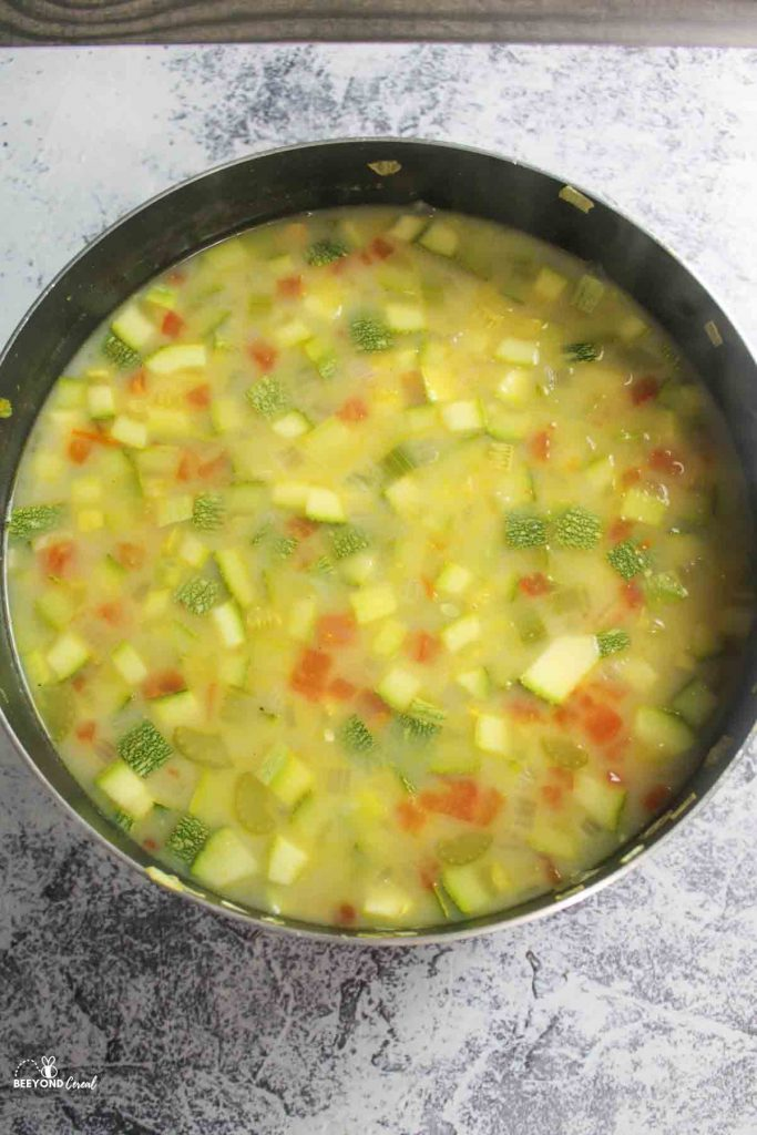 an aerial view into a pot filled with zucchini corn chowder