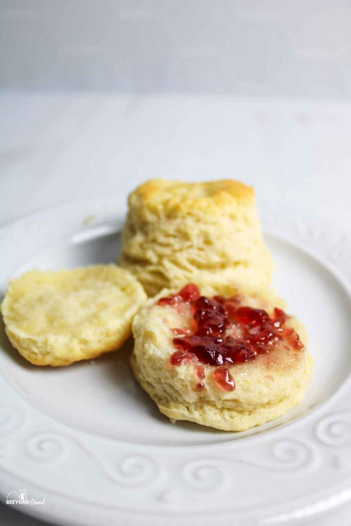 biscuits on a white plate, one split in half and topped with jam