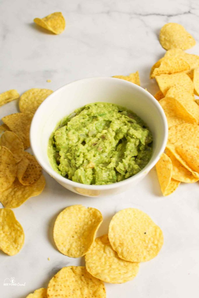 guacamole in a white bowl with chips around it