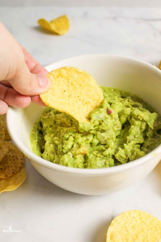 hand dipping chip into guacamole in a white bowl